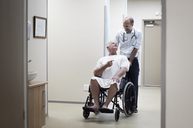 Doctor carrying patient on wheelchair in corridor - CAVF38467