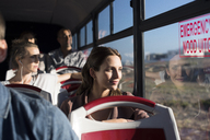 Passengers looking through window while traveling in tour bus - CAVF38521