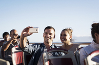 Couple taking selfie while traveling in double-decker bus against clear sky - CAVF38524