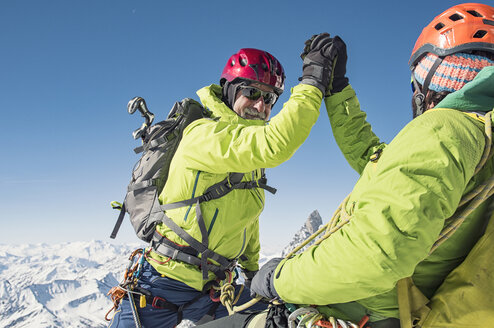 Hikers giving high-five while climbing mountain against clear blue sky - CAVF38539