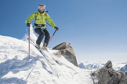 Hiker skiing on snow covered mountain against clear blue sky during sunny day - CAVF38560