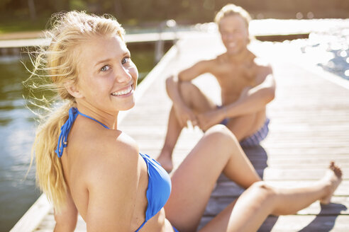 Portrait of smiling woman relaxing on boardwalk with man in background - MASF04628