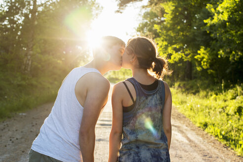 Rear view of couple kissing on dirt road against bright sun - MASF04634