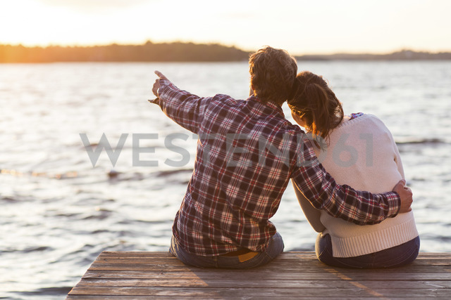 Rear view of man showing something to woman while sitting on pier against sea at sunset - MASF04649