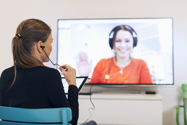 Rear view of businesswoman using in-ear headphones while video conferencing in creative office - MASF04658