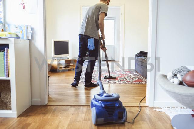 Rear view of man vacuuming carpet - MASF04661
