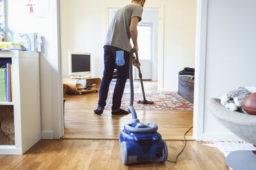 Rear view of man vacuuming carpet - MASF04661