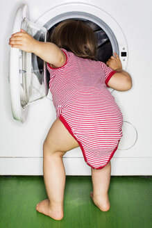 Rear view of baby girl peeking into washing machine at home - MASF04664
