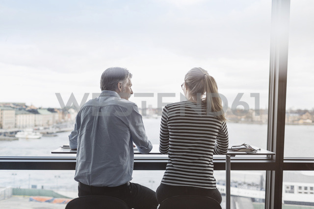 Rear view of business people sitting at counter by window in office - MASF04670