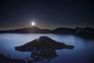 Idyllic view of Wizard Island amidst Crater Lake against sky during sunrise - CAVF38752