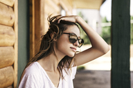 Beautiful woman with hand in hair outside log cabin during vacation - CAVF38848