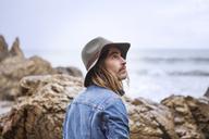 Thoughtful man by rocks on beach - CAVF38860