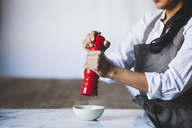 Midsection of woman using pepper mill in kitchen - CAVF38965