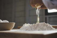 Cropped image of woman breaking egg in flour on table - CAVF38968