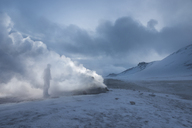 Man standing by fumaroles emitting steam on snow covered field - CAVF38977
