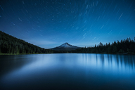 Scenic view of lake against star trails in sky at night - CAVF39064