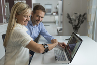 Man and smiling woman with wearable at her arm at desk - PAF01815