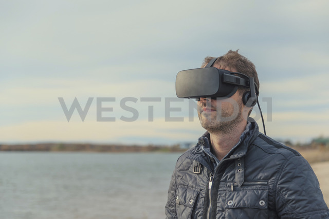 Man wearing VR glasses at lakeshore - PAF01824