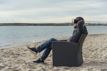 Man sitting in armchair on the beach wearing VR glasses - PAF01827