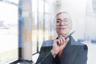 Portrait of confident businesswoman behind glass pane in office - UUF13327