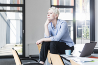 Smiling woman sitting on table in office - UUF13342