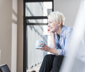 Smiling woman with cup of coffee sitting on table in office - UUF13345