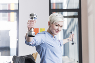 Portrait of smiling woman exercising with dumbbells in office - UUF13363