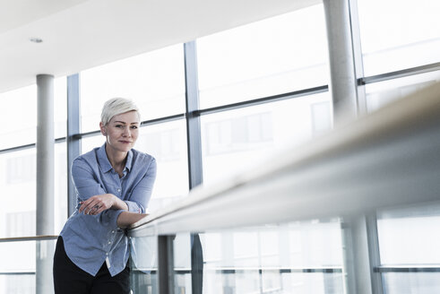 Portrait of woman in office building leaning on railing - UUF13366