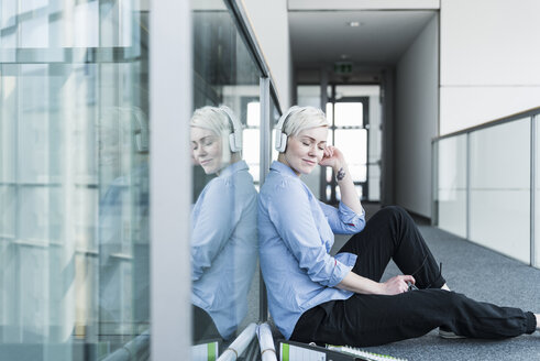 Woman sitting on office floor listening to music with headphones - UUF13369