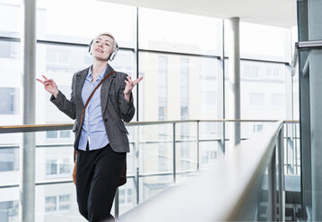 Woman on office floor enjoying listening to music with headphones - UUF13375