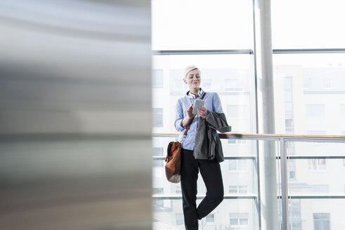 Smiling woman in office building using cell phone - UUF13378