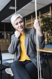 Portrait of smiling casual businesswoman sitting on swing in lounge - UUF13387