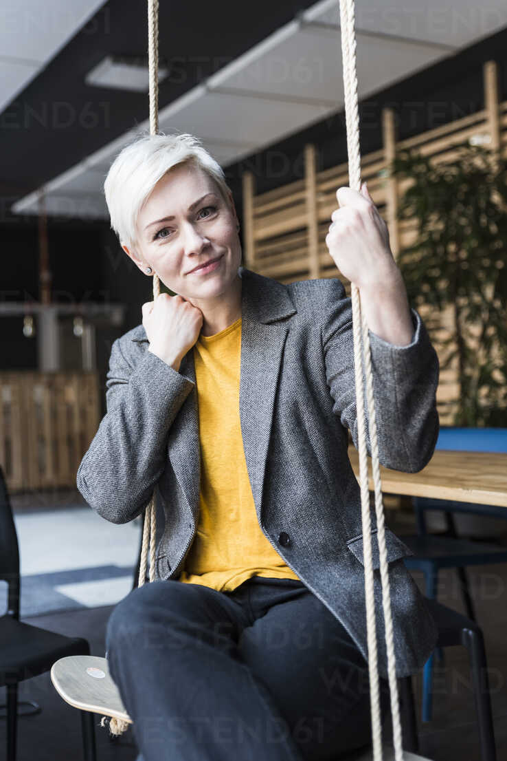 Portrait of smiling casual businesswoman sitting on swing in lounge - UUF13387 - Uwe Umstätter/Westend61
