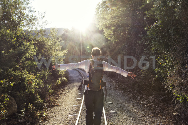 Greece, Pilion, Milies, back view of man with backpack balancing along rails of Narrow Gauge Railway - MAMF00050