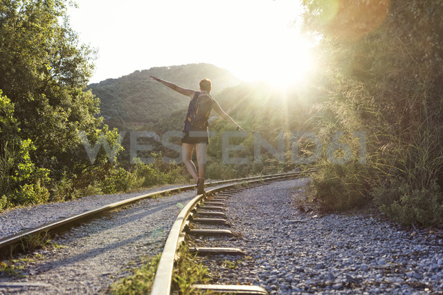 Greece, Pilion, Milies, back view of woman balancing along rails of Narrow Gauge Railway at sunset - MAMF00053