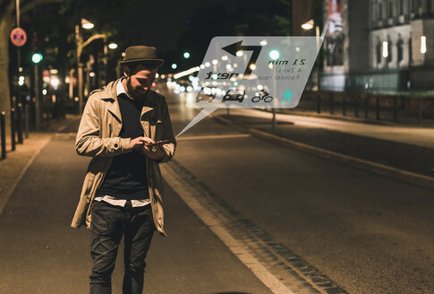 Young man on street at night with data emerging from smartphone - UUF13405