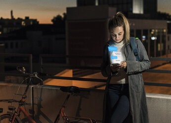 Young woman outdoors at night with text emerging from smartphone - UUF13411
