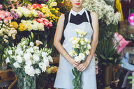Midsection of florist holding yellow roses at shop - CAVF39153