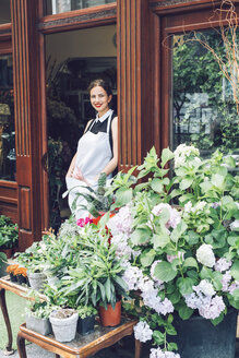 Portrait of smiling florist standing at entrance of shop - CAVF39159