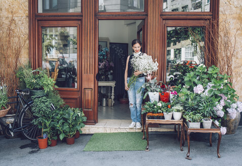 Female florist holding white flowers while standing entrance of shop - CAVF39177