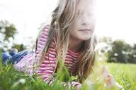Portrait of girl holding dandelion while lying on grassy field in park - CAVF39330
