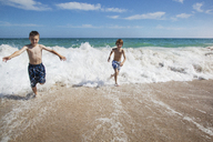 Cheerful brothers running at beach on sunny day - CAVF39339