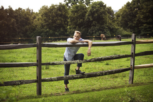 Man leaning on wooden fence at forest - CAVF39396