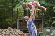 Happy father lifting daughter in backyard - CAVF39411