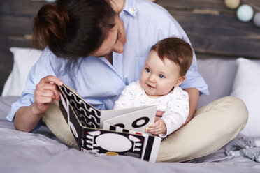 Mother and baby watching a picture book on bed at home - ABIF00307