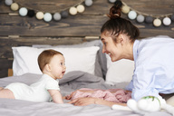 Mother and baby playing on bed at home - ABIF00319
