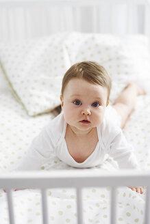 Portrait of baby lying in crib - ABIF00325