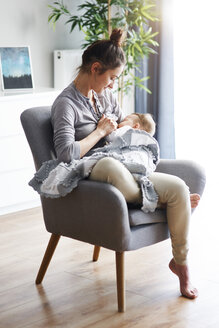 Mother sitting on armchair at home breastfeeding her baby - ABIF00328