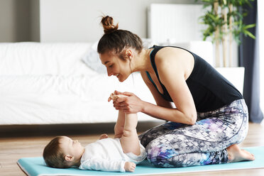 Mother with baby exercising on yoga mat at home - ABIF00334