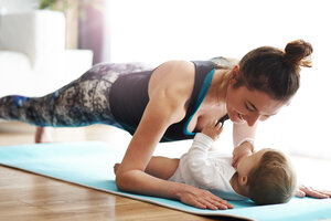 Mother with baby exercising on yoga mat at home - ABIF00337